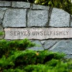 Serves unselfishly, in stone