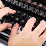 Female hands typing on the keyboard of the old mechanical typewriter.